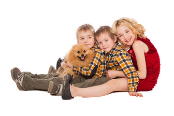 three children playing with little dog sitting on white backgrou