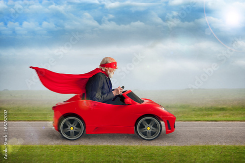 senior superhero driving a toy sports car - 66762002