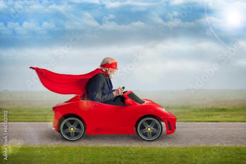 Leinwanddruck Bild senior superhero driving a toy sports car