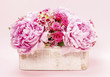 Pink peonies and roses in wooden box.