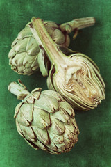 close up of a green fresh artichoke on a green background.