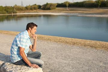 Junger Mann sitzt am See
