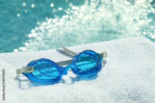 Leinwandbild Motiv Swimming goggles on towel