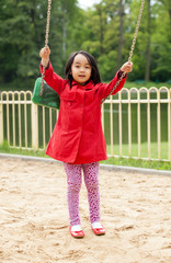 Little girl swinging on the playground