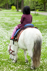 Little girl riding on a horse