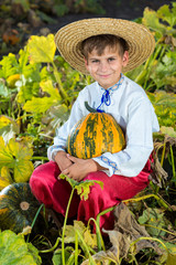 Smiling boy holding  big yellow pumpkin in hands