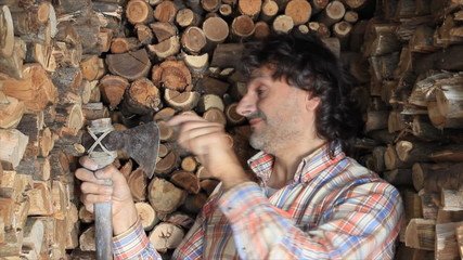 woodcutter sharpening an axe , huge firewood pile