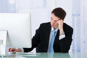 Worried Businessman Looking At Computer At Desk