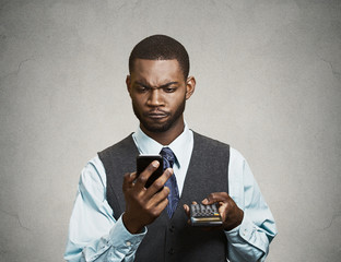 Man executive holding mobile phone, calculator, concerned