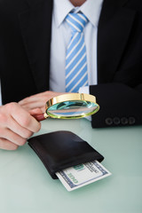 Businessman Examining Wallet With Magnifying Glass