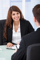 Businesswoman Interviewing Male Candidate At Desk