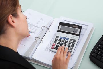 Businesswoman Calculating Bills At Desk