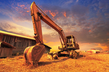 Old excavator standing with sunset background