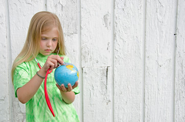 little girl with stethoscope on globe