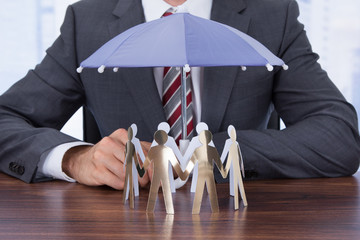 Businessman Sheltering Paper People With Umbrella