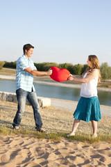 Paar zieht an rotem Herz