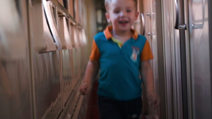 Happy boy running along the train hallway