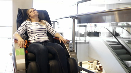 Woman having a rest in massage chair in the shopping center