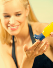 Young woman applying sun protection cream