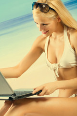 Young happy smiling woman in bikini with laptop