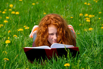 girl is reading in the spring- meadow