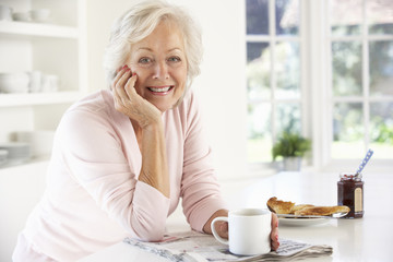 Retired woman eating breakfast
