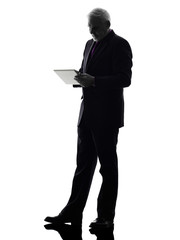 senior business man holding digital tablet silhouette