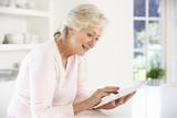Senior woman using tablet at home