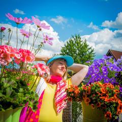 Frau sitzt zwischen Blumen auf dem Balkon
