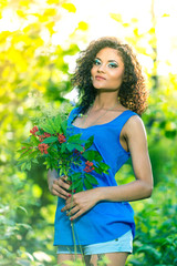 Young happy woman holding big bouquet of spring flowers outdoors