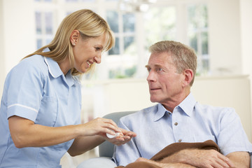 Senior man visited at home by nurse