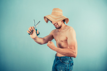 Silly man wearing hat is playing with scissors