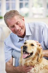 Senior man at home with dog