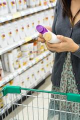 women comparing shampoo  in supermarket