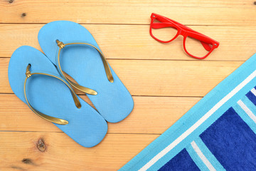 Beach slippers, towel and sunglasses on wood