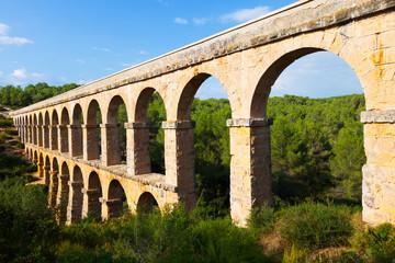 ancient  aqueduct in summer forest. Tarragona