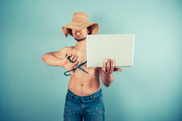 Young man wearing hat holding scissors and laptop