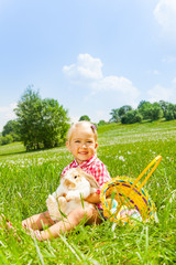 Happy small girl cuddles rabbit in green meadow
