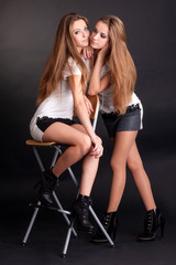 Two girls twins, isolated on black