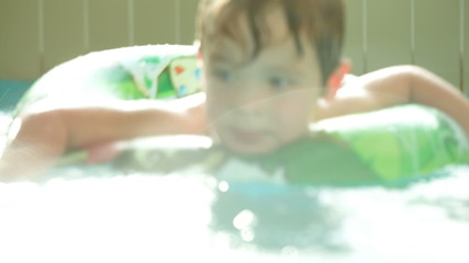 Cute child having fun swimming with rubber ring in the pool