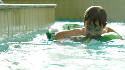 Boy with rubber ring swimming in water labyrinth