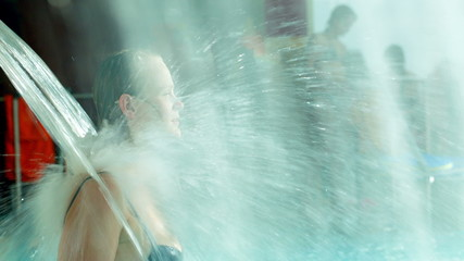 Woman refreshing under water shower in the pool
