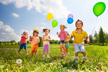 Children with colorful balloons running in field