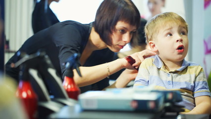 Little child getting his hair cut at the hairdressing saloon