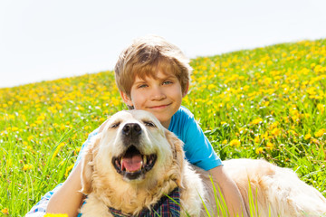 Smiling boy and funny dog sitting on grass