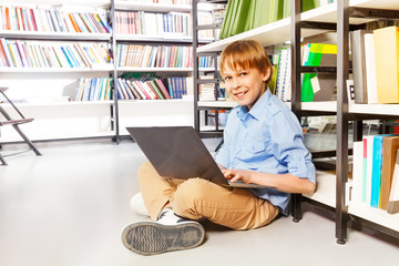 Happy boy sitting with laptop on the floor