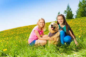 Two girls sitting near to dog on green grass