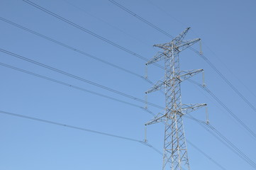 Power transmission tower against blue sky