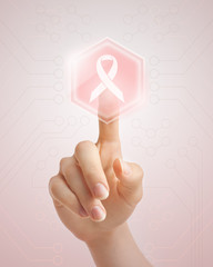 Hand pushing pink ribbon button