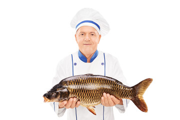 Mature chef holding an uncooked fish